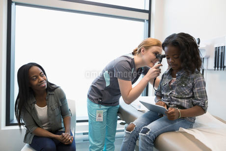 Female nurse with otoscope examining ear of girl patient using digital tablet in clinic exam roomの写真素材 [FYI02331144]