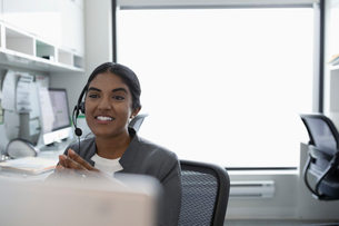 Smiling woman using hands-free telephone in clinic officeの写真素材 [FYI02331183]
