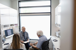 Male doctor talking with senior patient in clinic officeの写真素材 [FYI02331187]
