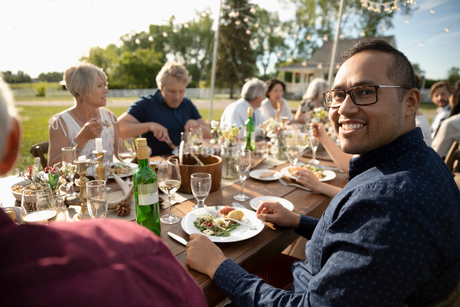 Portrait smiling man enjoying sunny garden party lunchの写真素材 [FYI02331200]