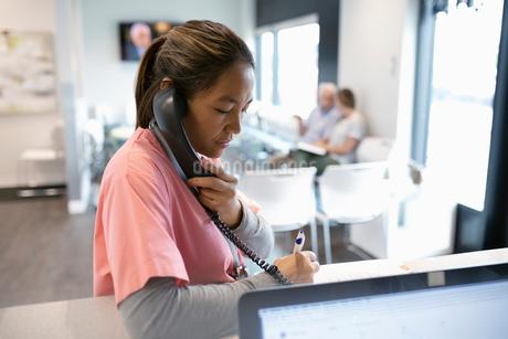 Female nurse talking on telephone at clinic reception deskの写真素材 [FYI02331231]