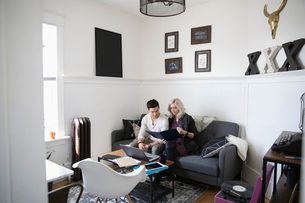 Young couple looking at finances in living roomの写真素材 [FYI02331238]