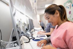 Smiling female nurse using computer in clinicの写真素材 [FYI02331258]