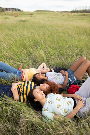 Carefree teenage girl friends laying in tall grassの写真素材 [FYI02331295]