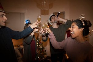 Festive millennial friends celebrating New Years Eve, toasting champagne flutesの写真素材 [FYI02331336]