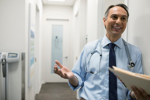 Smiling male doctor with medical record in clinic corridorの写真素材 [FYI02331343]