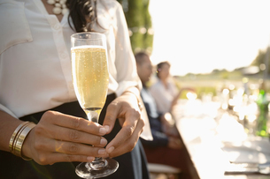 Close up woman drinking champagne at sunny garden partyの写真素材 [FYI02331356]