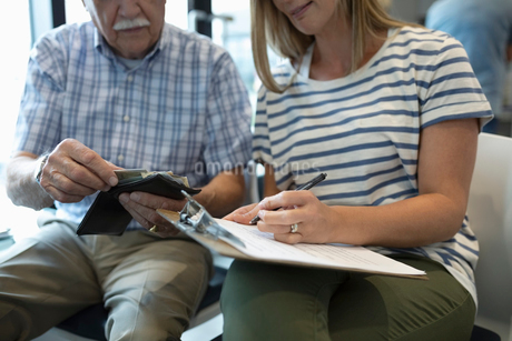 Close up daughter helping senior father fill out insurance paperwork in clinic waiting roomの写真素材 [FYI02331387]