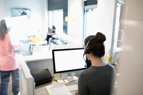 Receptionist working at computer at clinic receptionの写真素材 [FYI02331409]