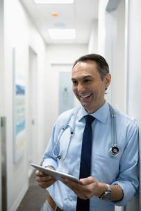 Smiling male doctor using digital tablet in clinic corridorの写真素材 [FYI02331420]