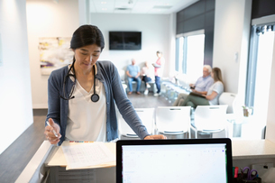 Female doctor reviewing medical record at clinic reception deskの写真素材 [FYI02331435]