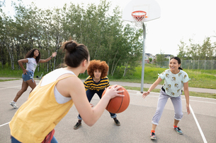 Teenage girl friends playing basketball at park basketball courtの写真素材 [FYI02331439]