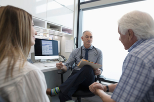 Male doctor with medical record talking to senior patient with daughter in clinic officeの写真素材 [FYI02331490]