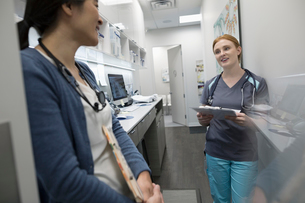 Female doctor and nurse discussing medical record in clinicの写真素材 [FYI02331517]