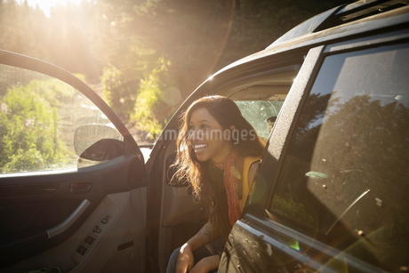 Smiling woman enjoying overland adventure, sitting in SUV in forestの写真素材 [FYI02331548]