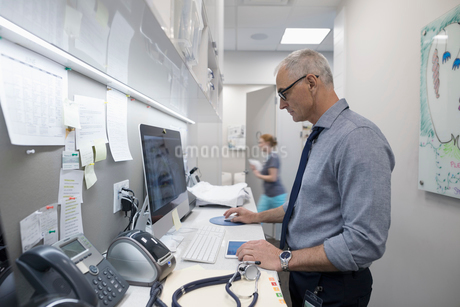 Male doctor using computer in clinicの写真素材 [FYI02331584]