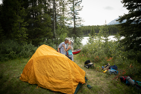 Affectionate mature couple kissing by tent at lakeside forest campsite, Alberta, Canadaの写真素材 [FYI02331593]