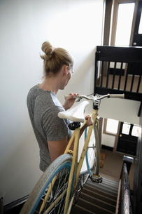 Young man carrying bicycle down apartment stairsの写真素材 [FYI02331631]