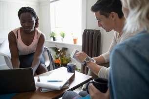 Financial advisor consulting with young couple in living roomの写真素材 [FYI02331638]