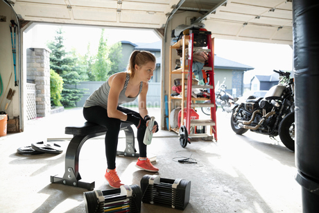 Young woman weightlifting, resting in garageの写真素材 [FYI02331661]