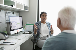 Female doctor talking with senior male patient in clinic officeの写真素材 [FYI02331692]