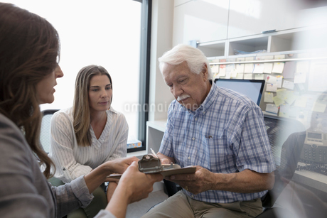 Female doctor guiding senior male patient with daughter signing paperwork in clinic officeの写真素材 [FYI02331704]