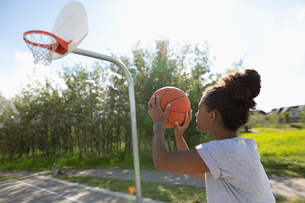 Young woman playing basketball at park basketball courtの写真素材 [FYI02331708]