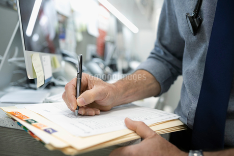 Close up male doctor writing in medical recordの写真素材 [FYI02331736]