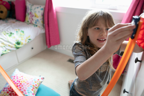 Girl playing with toy car track in bedroomの写真素材 [FYI02331782]