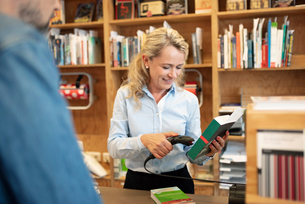 Female bookstore cashier scanning barcode on bookの写真素材 [FYI02331785]