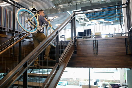Businessman carrying bicycle up office stairsの写真素材 [FYI02331835]