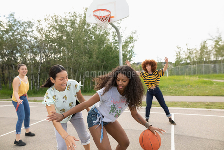 Teenage girl friends playing basketball at park basketball courtの写真素材 [FYI02331843]