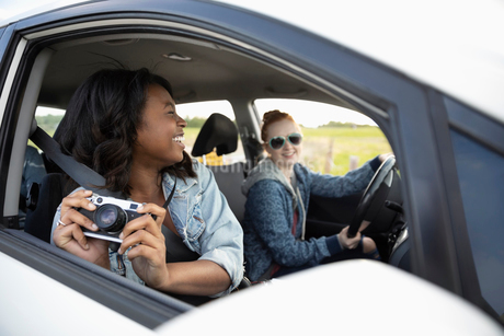 Carefree young woman in car enjoying road trip with friends, using cameraの写真素材 [FYI02331846]