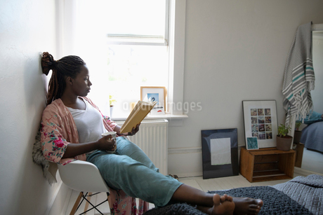 Young woman relaxing, drinking coffee and reading book in bedroomの写真素材 [FYI02331855]