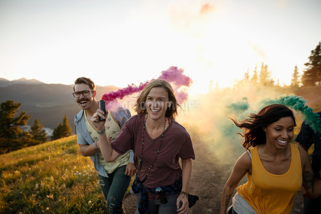 Playful friends enjoying colorful smoke bombs on sunny mountain roadの写真素材 [FYI02331858]