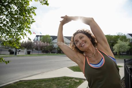 Smiling senior female runner stretching arms on sunny neighborhood sidewalkの写真素材 [FYI02331869]