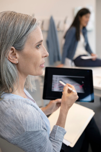 Female doctor discussing x-ray on digital tablet in clinicの写真素材 [FYI02331903]