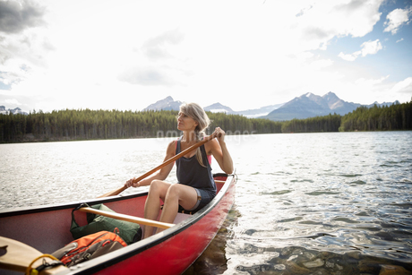 Serene mature woman canoeing on tranquil lake, Alberta, Canadaの写真素材 [FYI02331911]