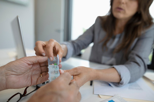Close up female doctor showing prescription medicine pill box to patientの写真素材 [FYI02331930]