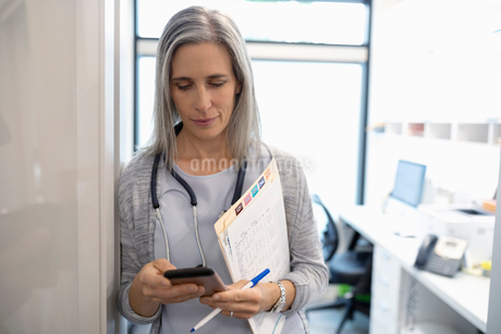 Female doctor with smart phone and medical record in clinic doorwayの写真素材 [FYI02331945]