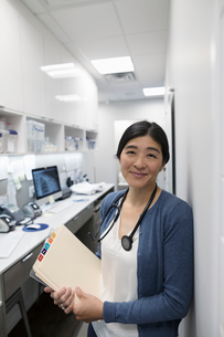 Portrait smiling, confident female doctor with medical records in clinicの写真素材 [FYI02331954]
