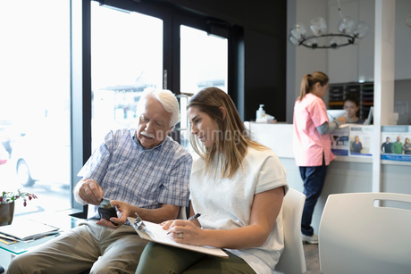 Daughter helping senior father fill out insurance paperwork in clinic waiting roomの写真素材 [FYI02331988]