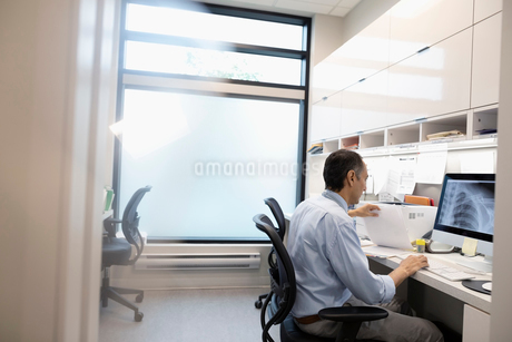 Male doctor reviewing x-ray on computer in clinic officeの写真素材 [FYI02331995]