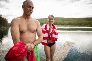 Portrait mature couple with towels on diving board above lake, Alberta, Canadaの写真素材 [FYI02332010]