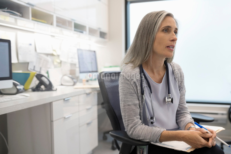 Focused female doctor talking in clinic officeの写真素材 [FYI02332016]