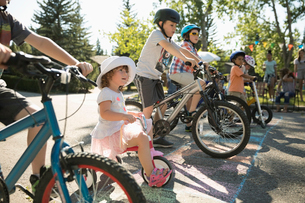Kids on bicycles ready for race at starting line at summer neighborhood block partyの写真素材 [FYI02332032]