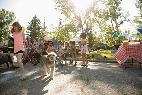 Kids and dog parade at summer neighborhood block party in sunny parkの写真素材 [FYI02332091]