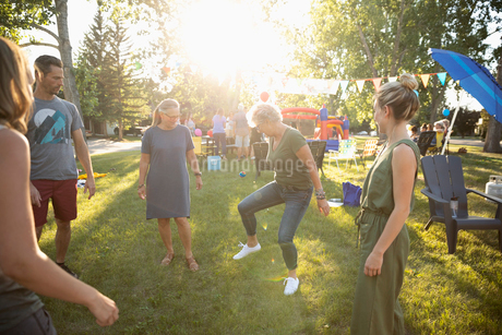 Neighbors playing with hacky sack at summer neighborhood block party in sunny parkの写真素材 [FYI02332129]
