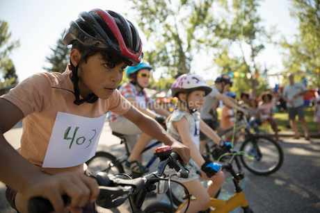 Focused, determined boy at starting line ready for bike race at summer neighborhood block partyの写真素材 [FYI02332167]