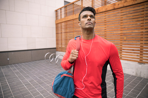 Confident, athletic man with gym bag listening to music with headphonesの写真素材 [FYI02332286]